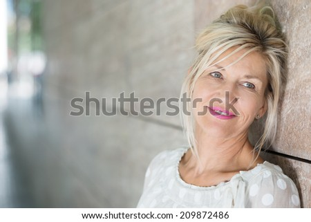 Contemplative beautiful middle-aged blond woman leaning against a receding angled wall staring into the distance with a pensive expression - stock photo