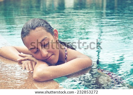 Contemplative young Asian woman in a sparkling blue swimming pool resting her head on her arms on the pool surround with closed eyes - stock photo