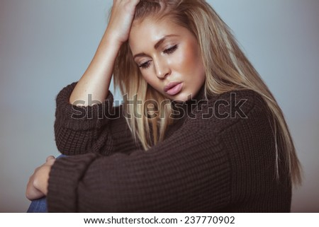 Contemplative young woman in sweater. Pretty young woman looking down in thought. - stock photo