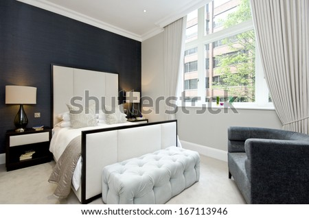 Contemporary and luxutious double bedroom with large bed and contemporary designer furniture - stock photo