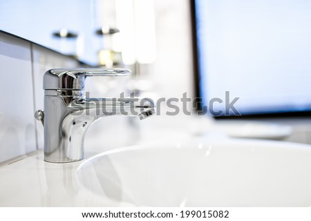 Contemporary bathroom sink taps and mirrors in luxury home or hotel - stock photo