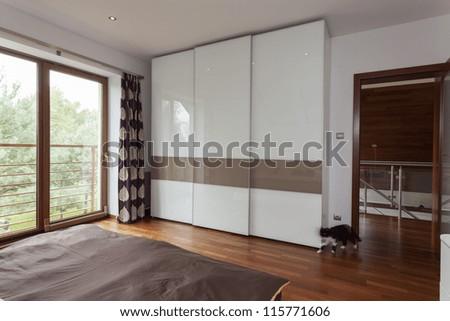 Contemporary bedroom with balcony and huge wardrobe - stock photo