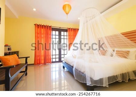 Contemporary bedroom with mosquito netting at Banana Garden Beach, Koh lanta, Krabi, Thailand. - stock photo