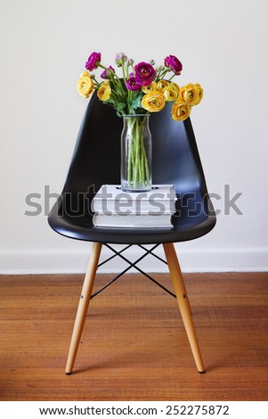 Contemporary black dining chair with vase of yellow and purple flowers - stock photo