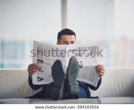 Contemporary businessman reading newspaper in office