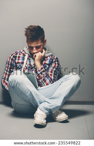 Contemporary casual young man in jeans and sneakers sitting cross legged on the floor using a tablet reading or studying information with a serious engrossed expression