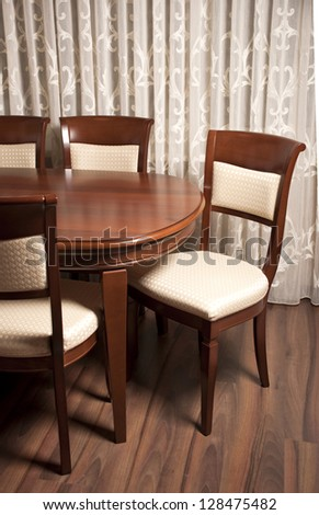 Contemporary dining room, a table with chairs in the foreground - stock photo