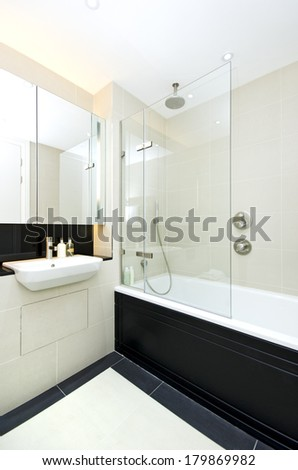 Contemporary ensuite family bathroom with modern bath tub with glass panel, ceramic wash basin and mirror in beige - stock photo