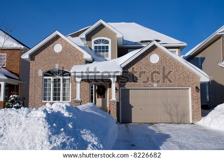 contemporary 2 floor beige brick house with attached garage in winter; front view against deep blue sky - stock photo