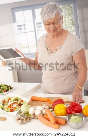 Contemporary grandmother cooking healthy food, using tablet computer to prepare meal. - stock photo