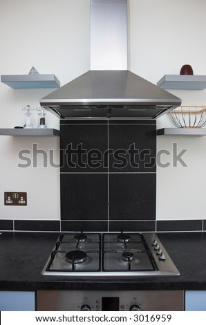 Contemporary kitchen interior detail showing stove top and extractor stainless steel appliances. - stock photo