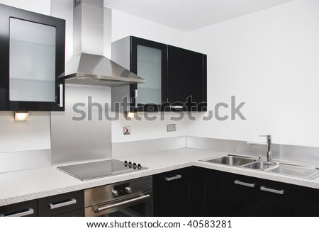 contemporary kitchen with a black piano finish and granite worktop - stock photo