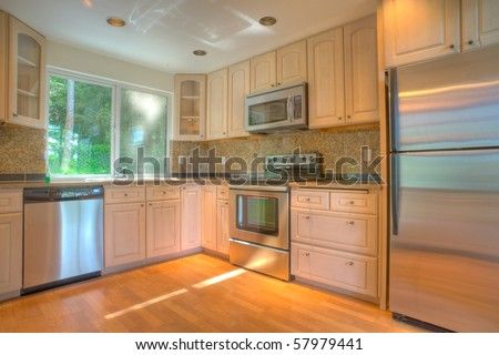 Contemporary kitchen with stainless steel appliances and granite counters - stock photo