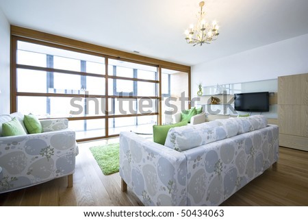 Contemporary living area with designer furniture, with green fragments and  floor to ceiling windows - stock photo