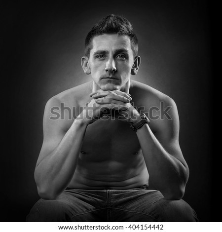 Contemporary man in jeans sitting - stock photo