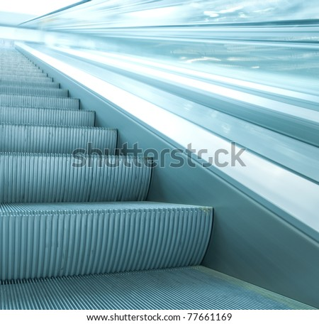 contemporary moving escalator stairs inside business blue hall - stock photo