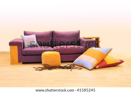 Contemporary purple upholster sofa with pillows decoration - stock photo