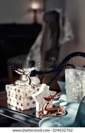 Contemporary style Christmas decor - ceramic reindeer and gift boxes on coffee table in bright light from the window, in dim lit room. Natural light. Toned photo. Shallow focus on the copper reindeer. - stock photo