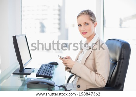 Content blonde businesswoman in bright office text messaging