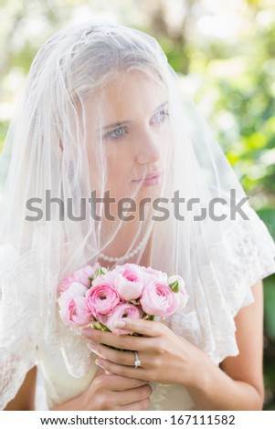 Content bride wearing veil over face holding rose bouquet in the countryside