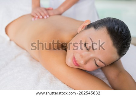 Content brunette enjoying a back massage at the health spa
