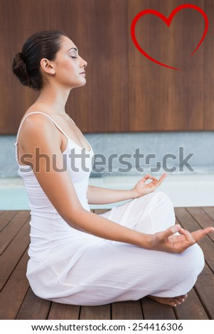 Content brunette in white sitting in lotus pose against heart - stock photo