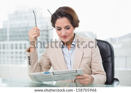 Content businesswoman reading newspaper in bright office - stock photo