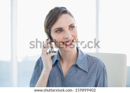 Content lovely businesswoman phoning with her smartphone sitting at her desk in the office - stock photo