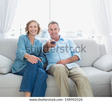 Content middle aged couple sitting on the couch watching tv at home in the living room