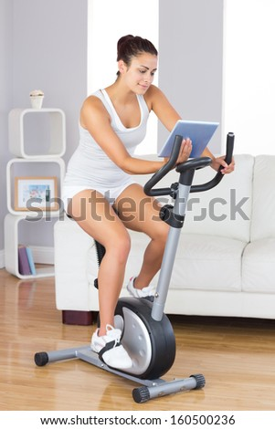 Content slim woman using her tablet while training on an exercise bike in the living room - stock photo