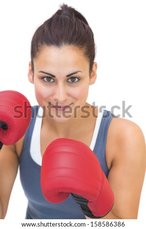 Content sporty brunette wearing red boxing gloves on white background