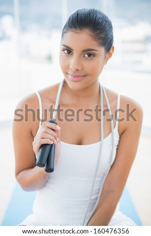 Content toned brunette sitting on floor with skipping rope in bright room