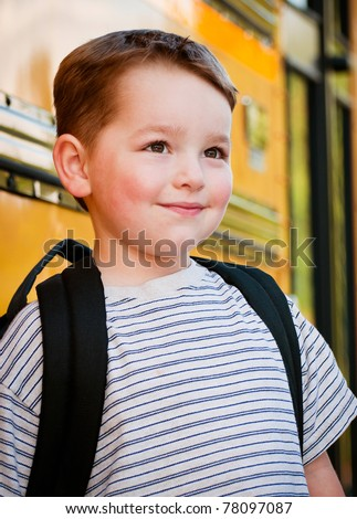 Content young boy in front of yellow school bus waiting to board on first day back to school. - stock photo