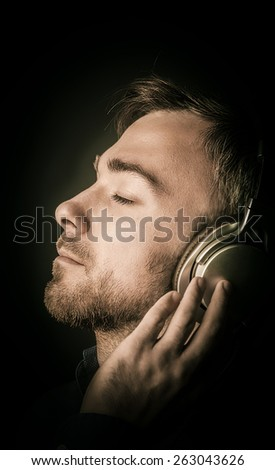 Contented attractive young man listening to his music on stereo headphones with his eyes closed in pleasure, closeup side view of his face over black - stock photo