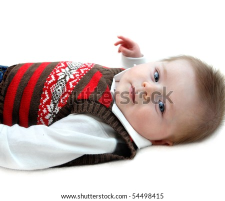 Contented baby boy lies on all white carpeted floor.  Image is isolated and baby is looking with eyes wide open.  He is wearing jeans and sweater vest. - stock photo
