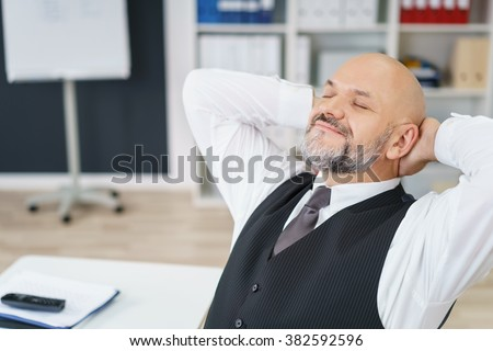 Contented businessman relaxing in the office reclining in his chair with his hands clasped behind his head and eyes closed smiling in pleasure - stock photo