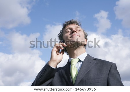 Contented businessman using mobile phone against cloudy sky