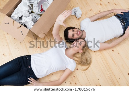 Contented young couple relax on the wooden floor in their new home alongside a packing carton visualizing their new decor and framing it with their hands, view from above - stock photo