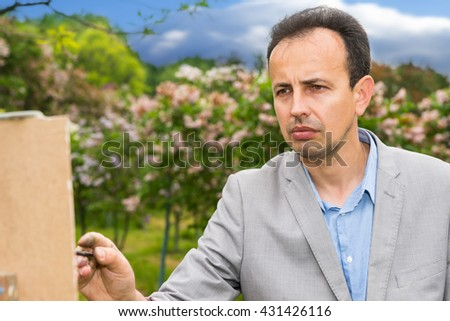 Conteplative middle-aged fashionable handsome male artist during painting on a sketchbook in a park - stock photo