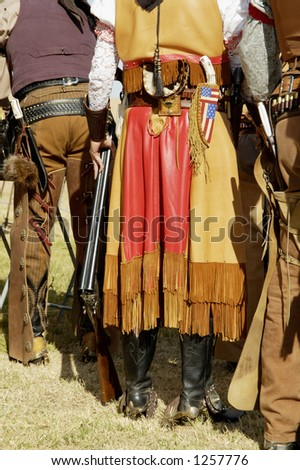 Contestants in period dress wait to compete in a cowboy action shooting event. - stock photo