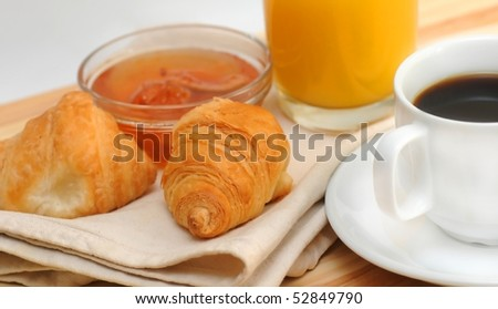 Continental breakfast - croissant, coffee, jam and orange juice - stock photo