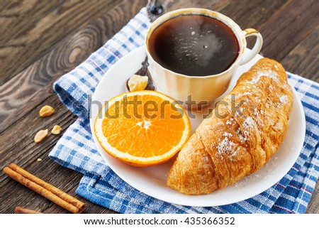 Continental breakfast - cup of hot coffee, croissant and orange. Tasty food on plaid blue napkin, rustic wooden background. - stock photo