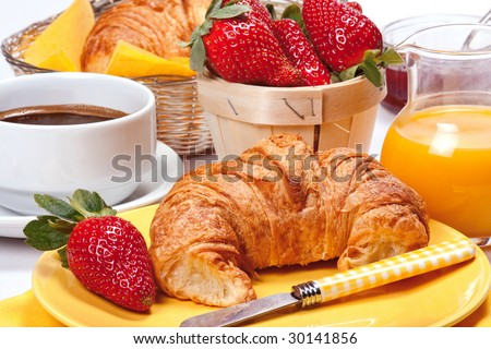 Continental breakfast. Freshly baked croissants with jam, strawberries, coffee and orange juice.