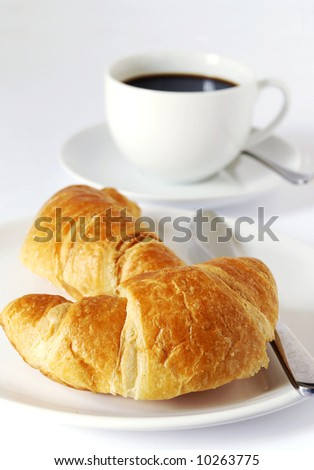 continental breakfast of coffee and croissants - stock photo