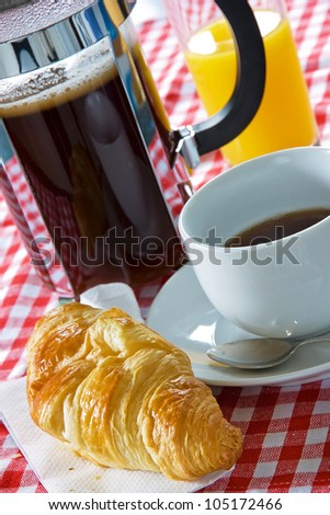 Continental breakfast with croissant, coffee cup and cafetiere - stock photo