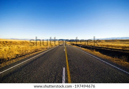 Continuous road in a scenic with mountain ranges afar. - stock photo