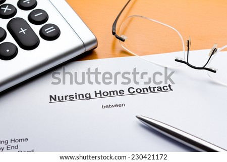 Contract about a nursing service on an outpatient basis with calculator, pair of glasses and ballpoint pen - stock photo