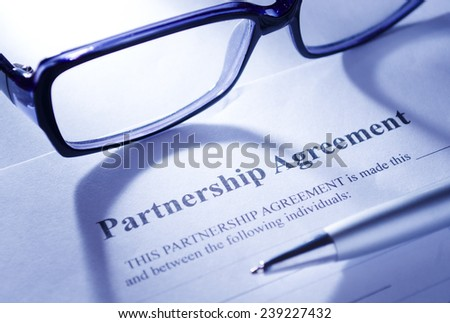 Contract Concept - Conceptual Close up of Eyeglasses and Ballpoint Pen on Top of Partnership Agreement Paper Placed on White Table. - stock photo