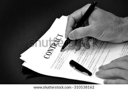 Contract on desk with black pen being signed by person - stock photo