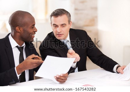 Contract on good conditions. Two cheerful business people in formalwear discussing something and pointing a paper - stock photo